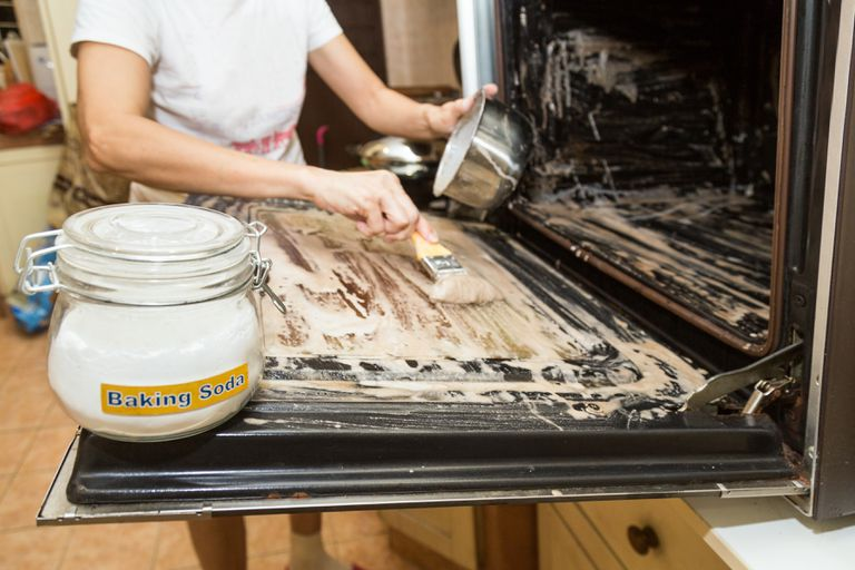 Person applying mixed baking soda onto surface of oven