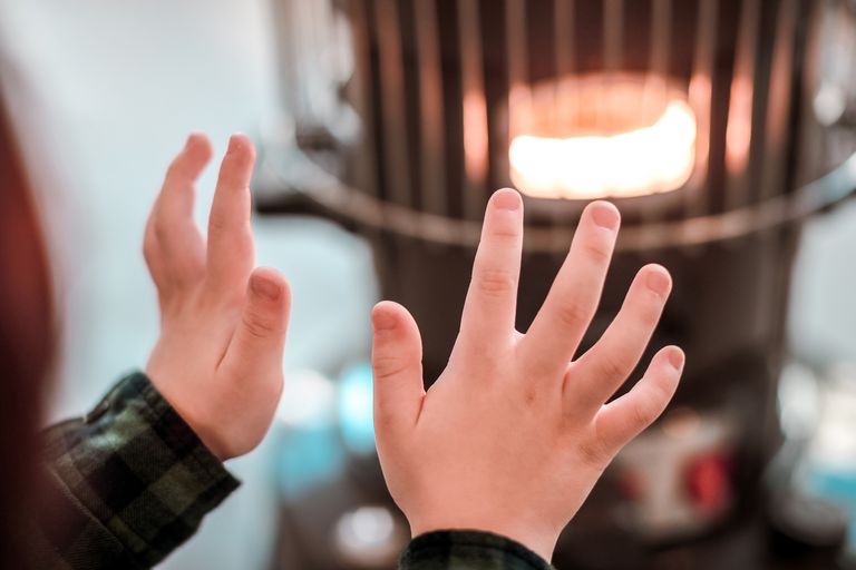 A young boy warming his hands by a kerosene heater