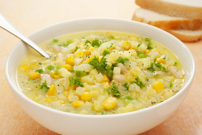 Bowl of corn chowder with corn, potatoes, and parsley