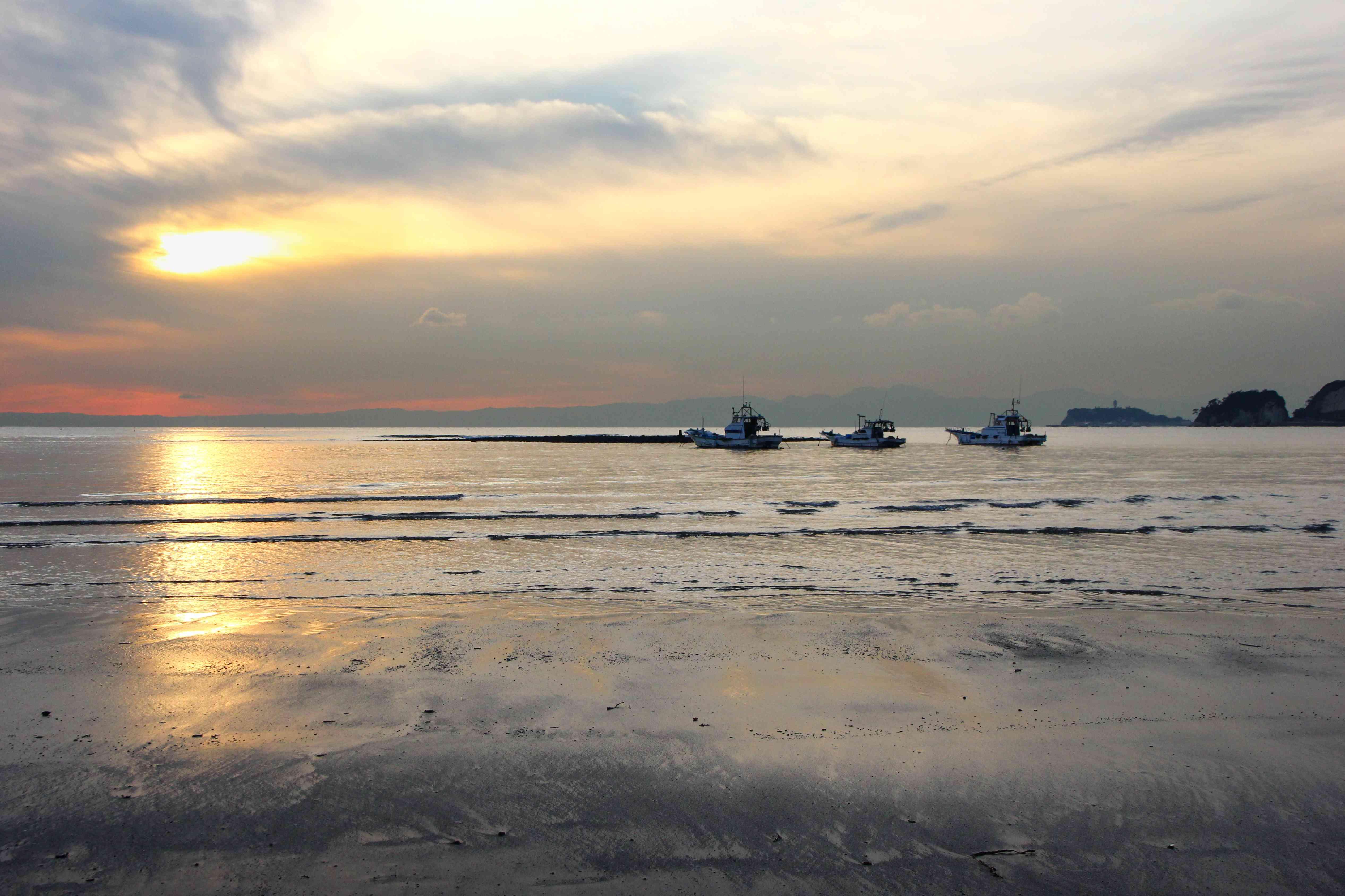 3 boats on right horizon as sun sets on ocean beach