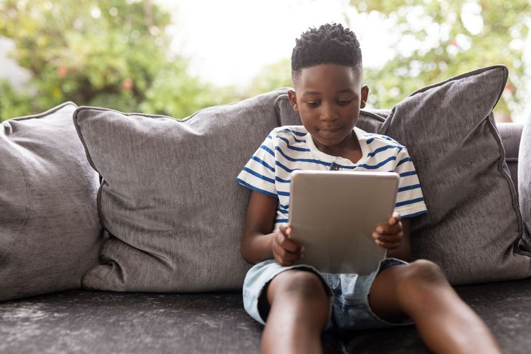 Boy using digital tablet on a sofa in living room