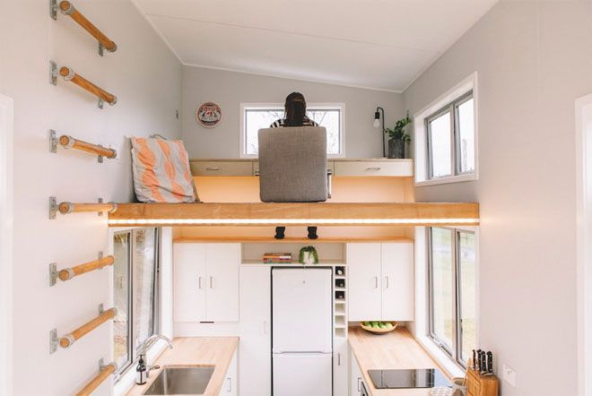 Woman sitting in chair at work space, feet visible on top of the kitchen cabinets