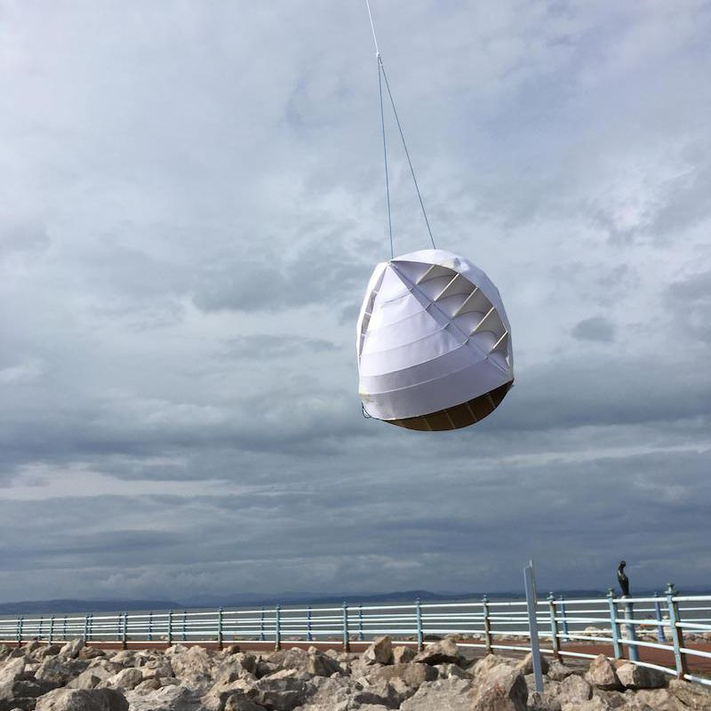 A cardboard prototype of the O-Wind Turbine being tested on the British seashore.