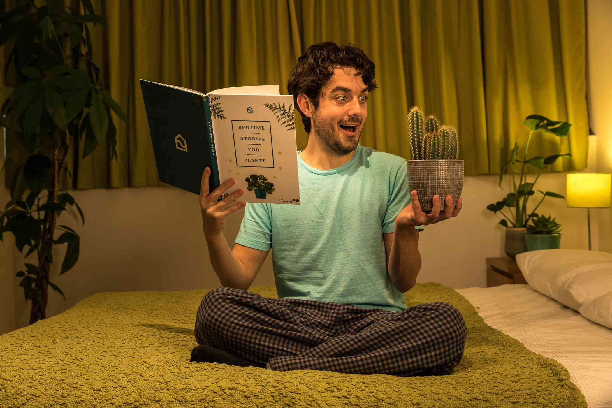 a man holds a book and plant in his hands while in bed