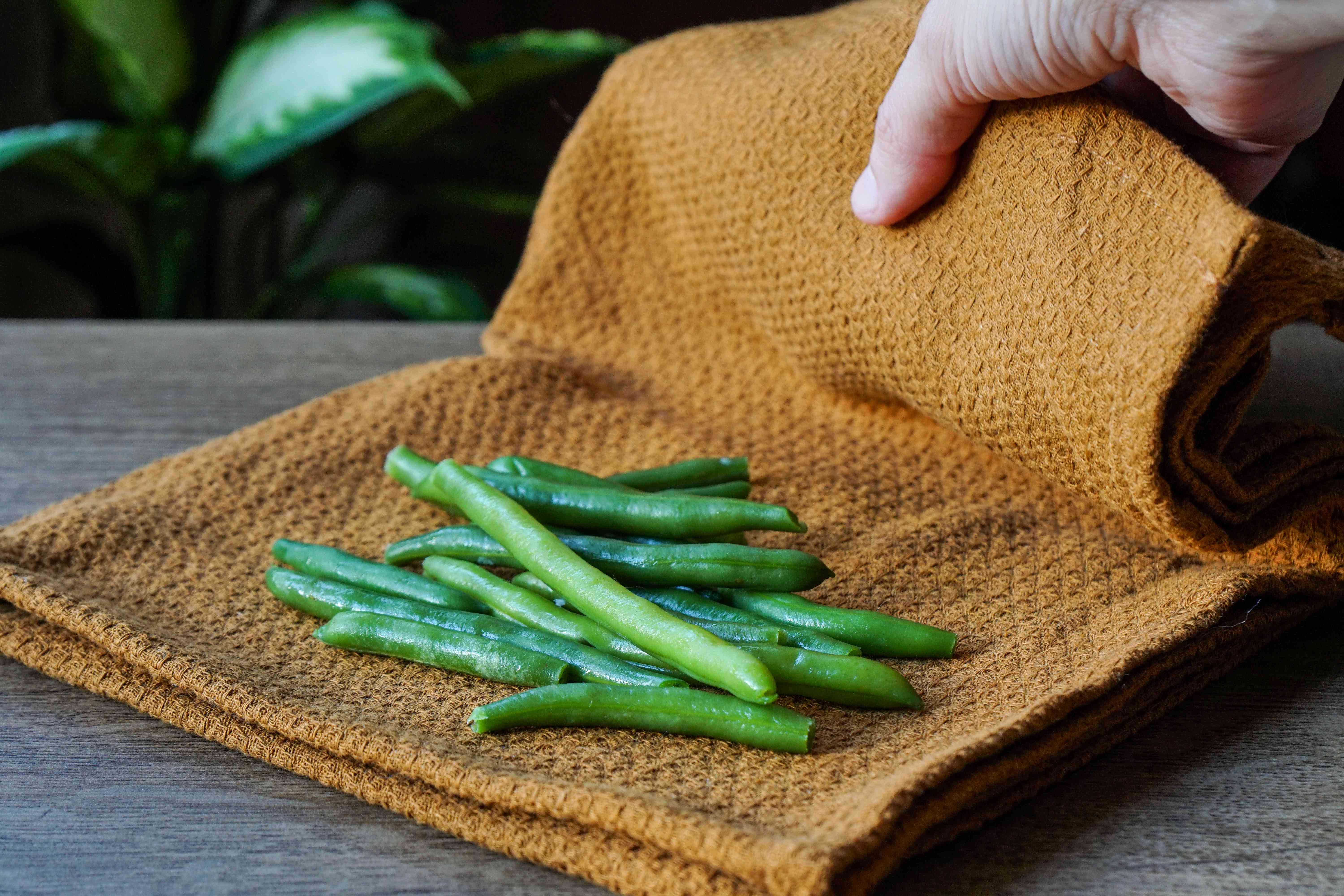 fresh green beans are placed in damp brown fabric for plastic-free storage