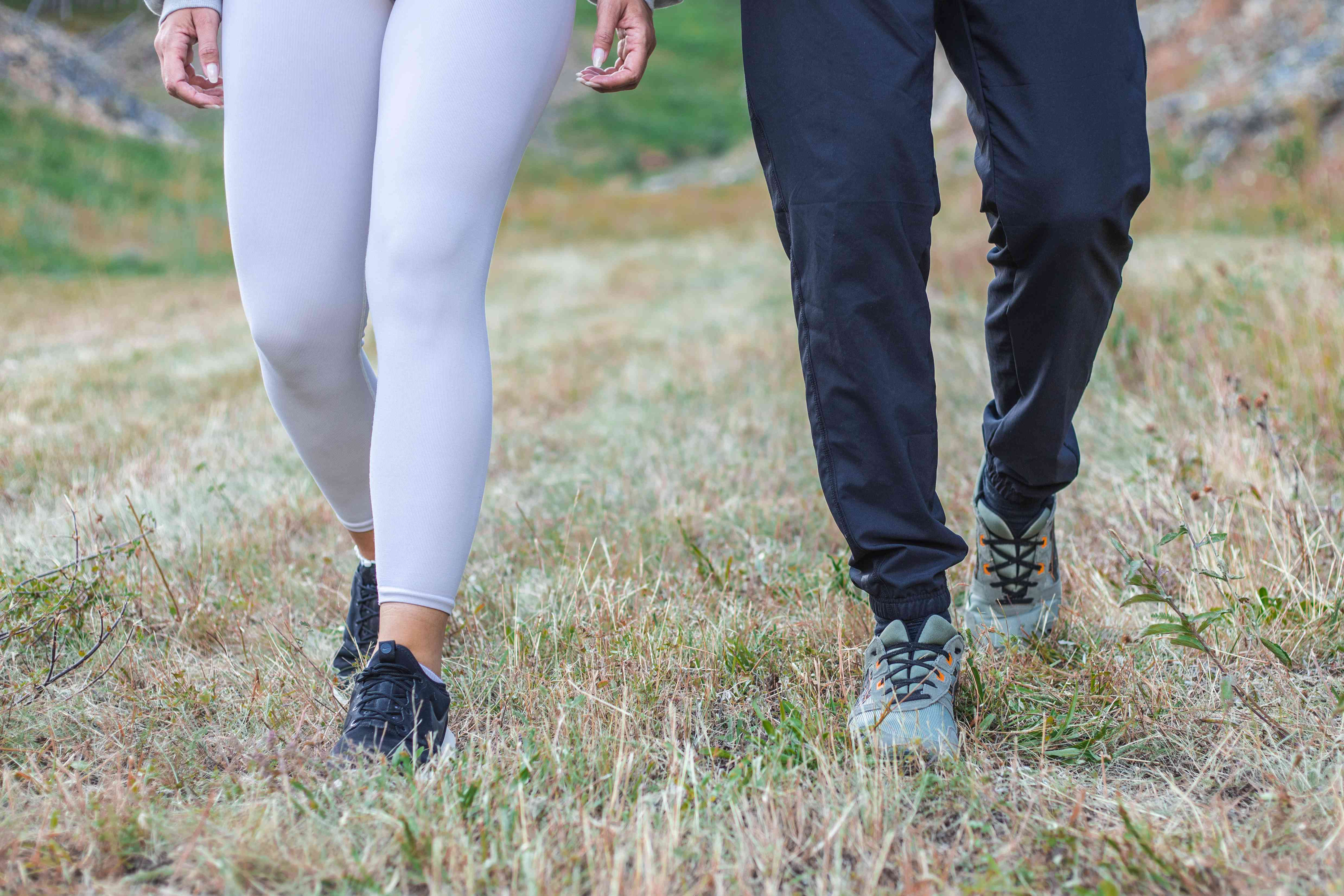 woman and man in exercise clothes walk on grassy trail with hill in background