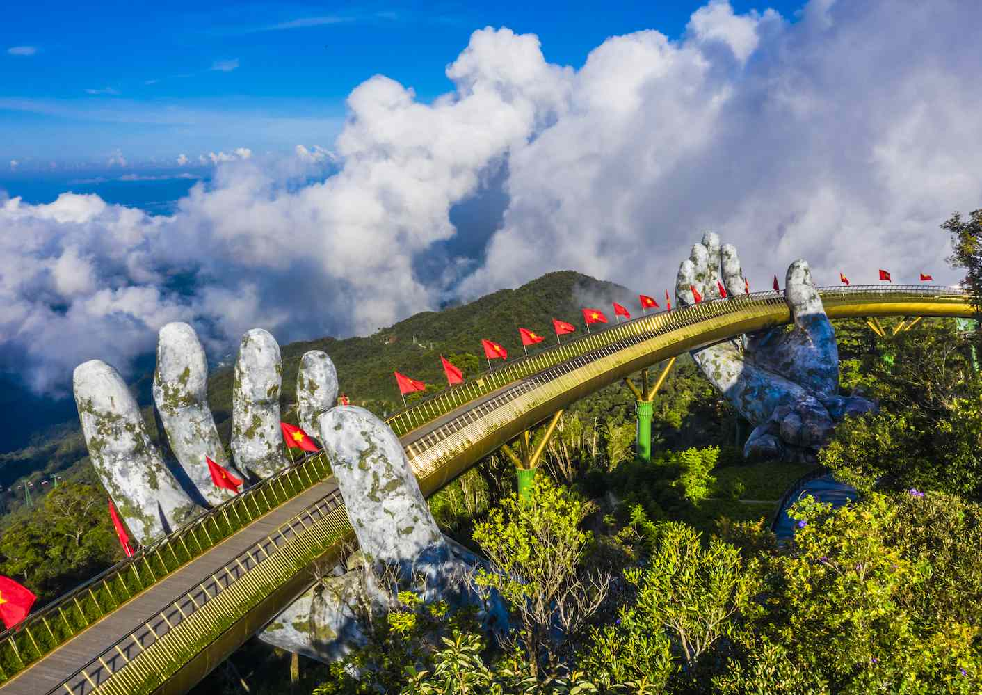 The gold-painted Cau Vang bridge in Vietnam appears to be held by two giant hands of stone