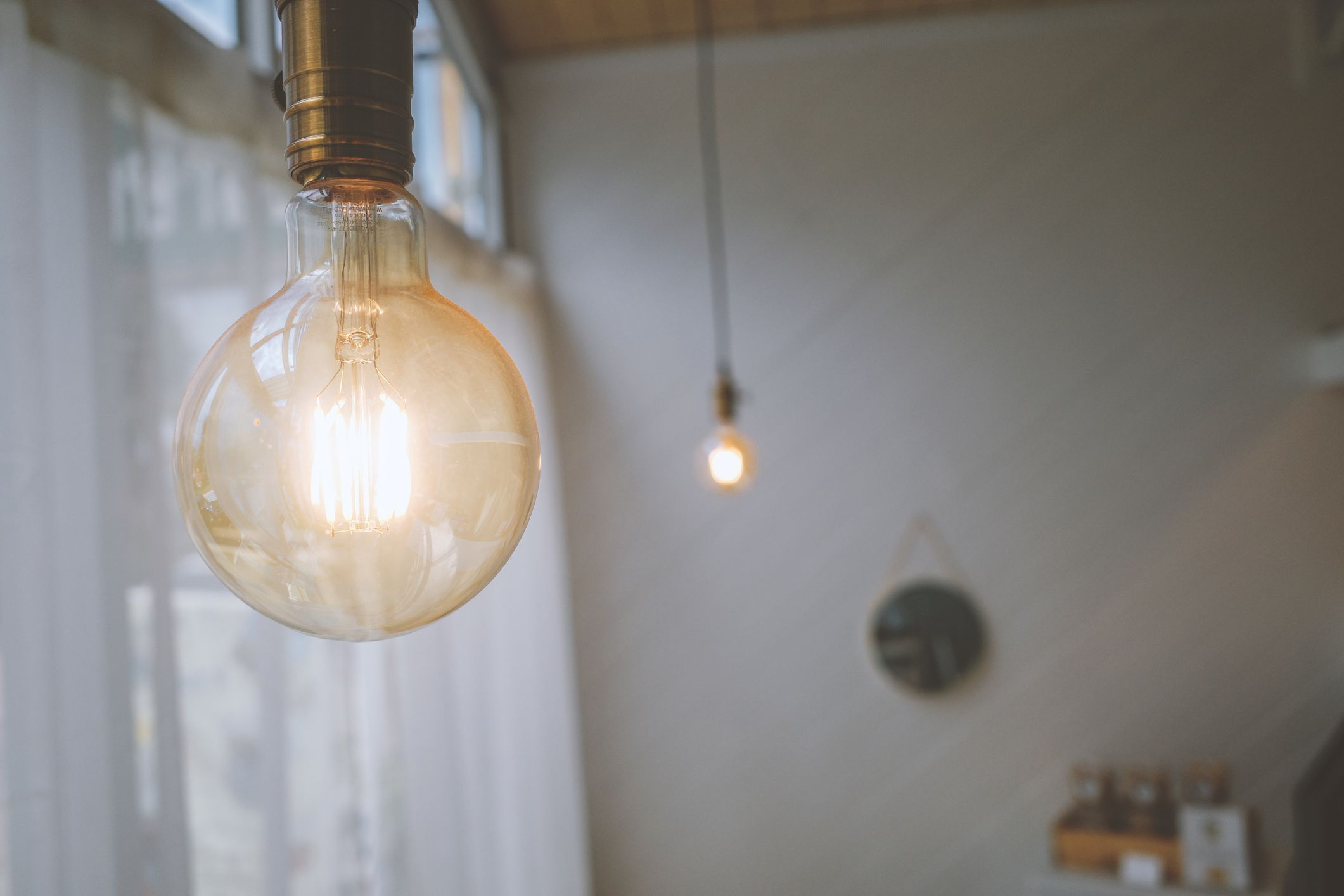 Incandescent light bulbs hang from a ceiling.