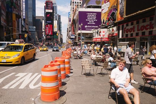 Busy street scene with people sitting in chairs