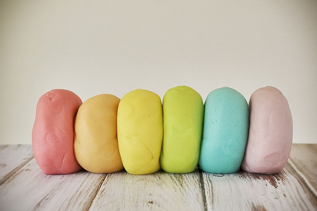 Rainbow colors of homemade playdough lined up on a wooden table