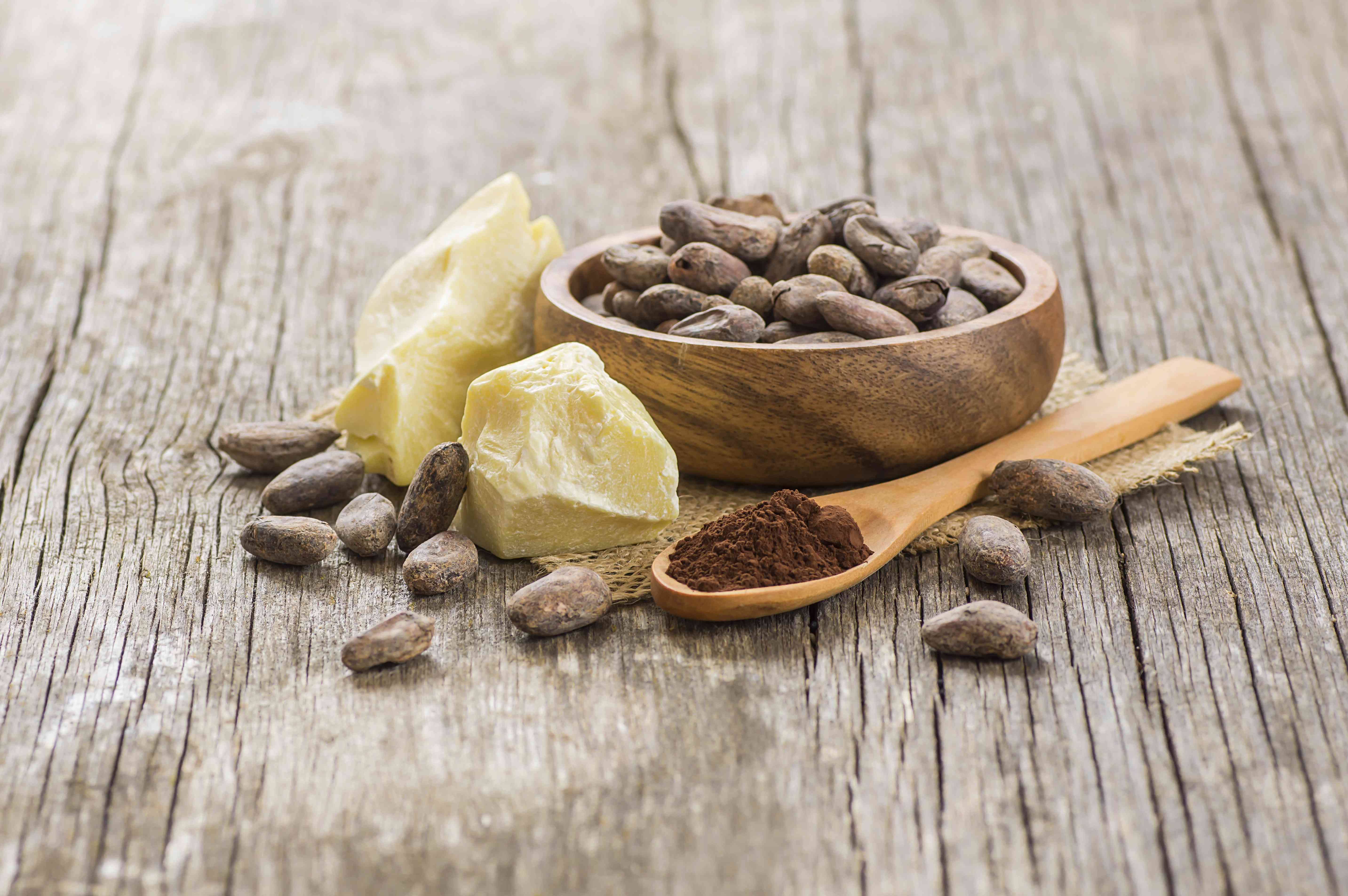 Cocoa butter or Cocoa bean solid oil with cacao powder in spoon and raw cocoa beans in wooden bowl on rustic backdrop.