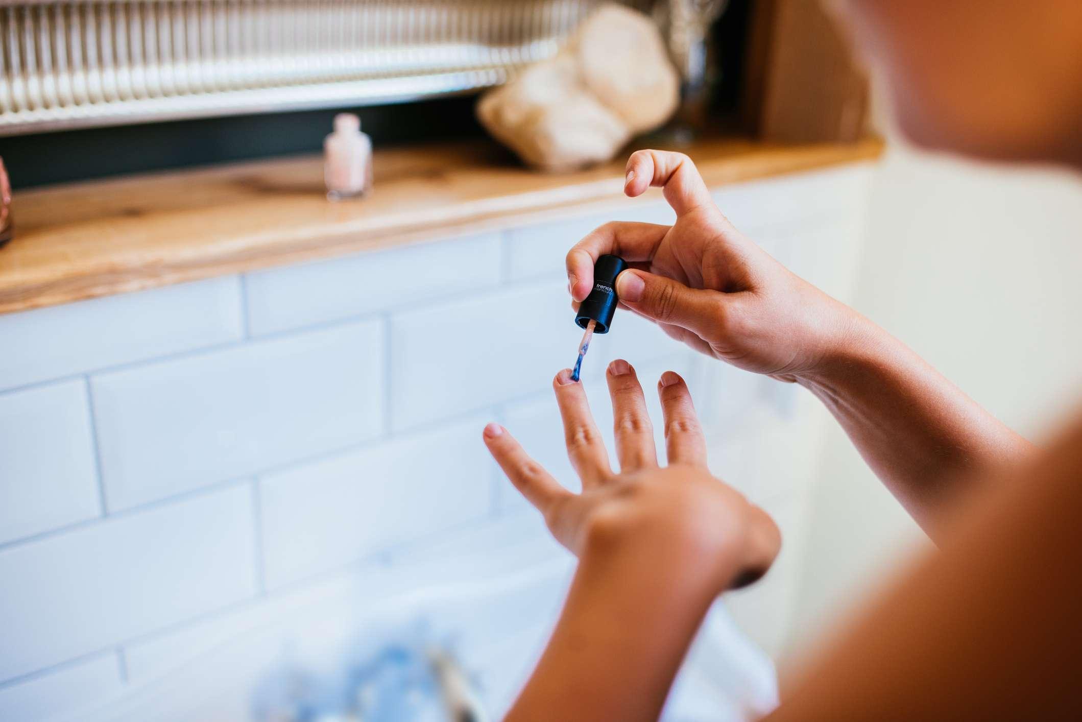 A woman applies nail polish in her bathroom.