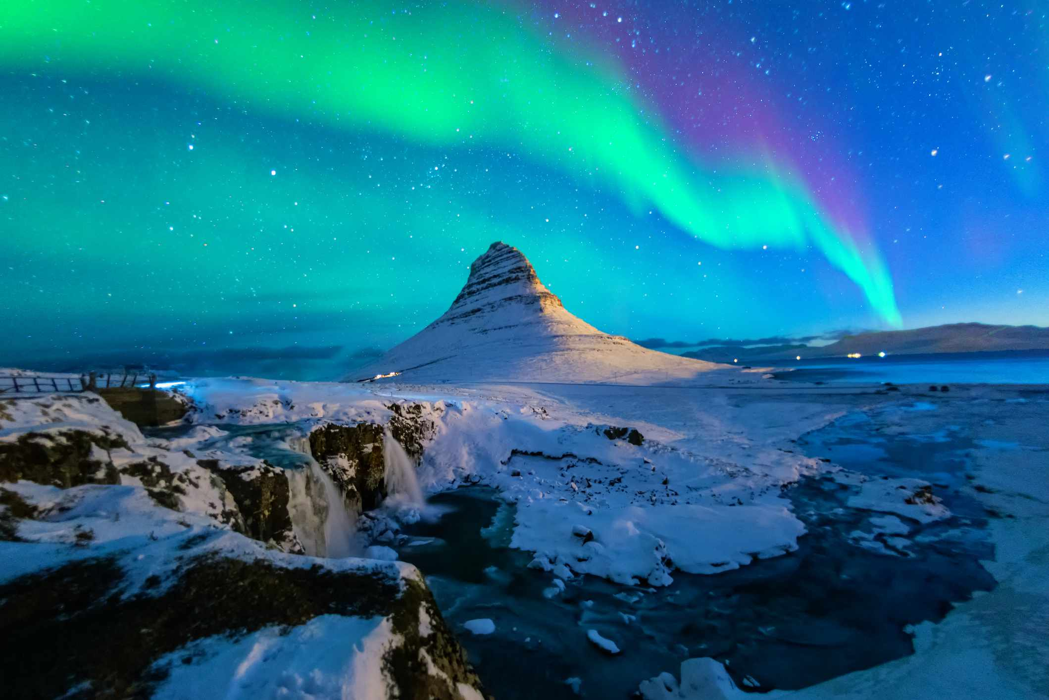 Multicolored northern lights over a snowy Mount Kirkjufell