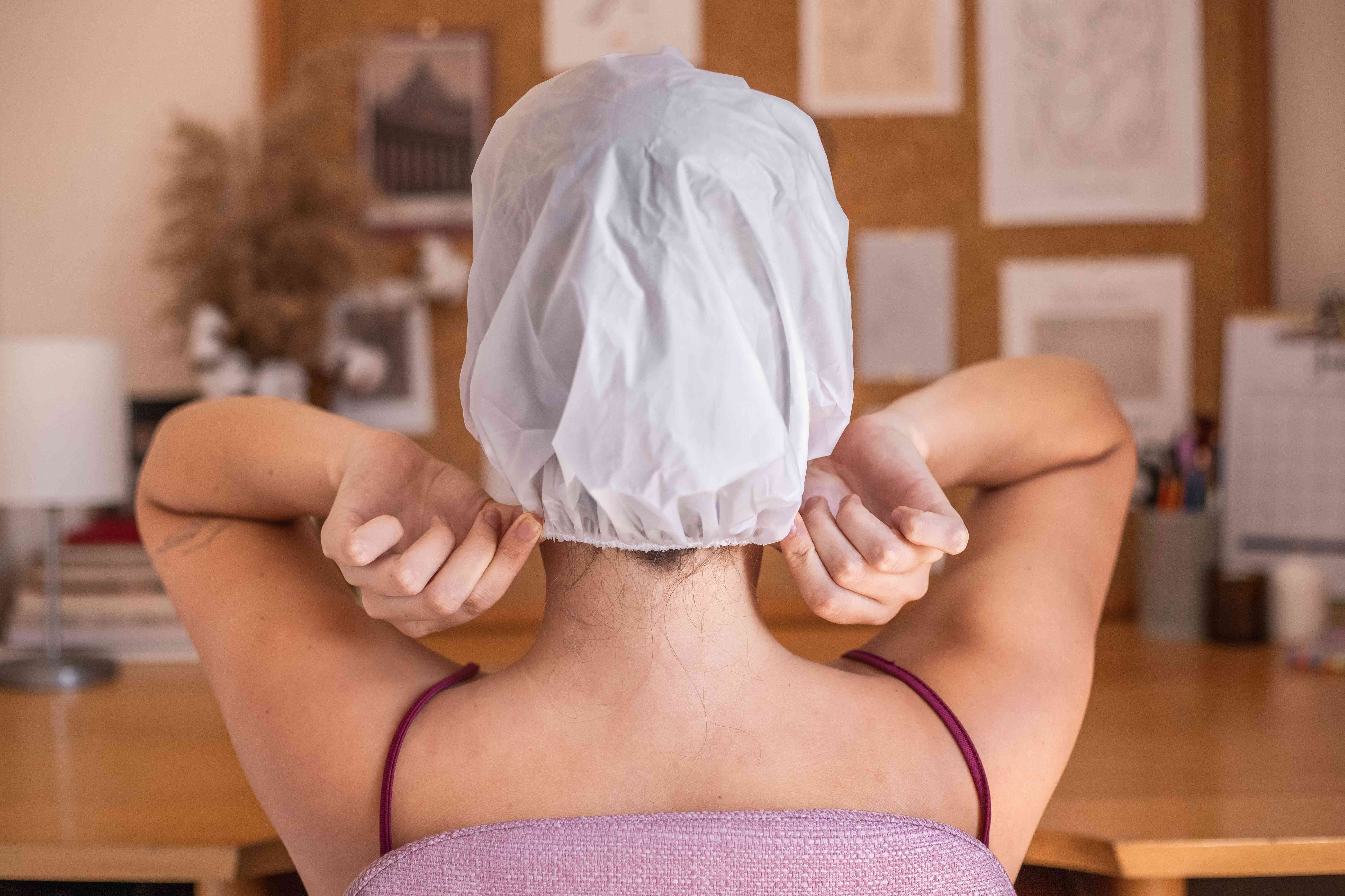 woman puts shower cap over hair to let olive oil mask soak in
