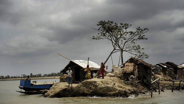 Bangladeshi villagers stand atop an embankment following Cyclone Aila in 2010