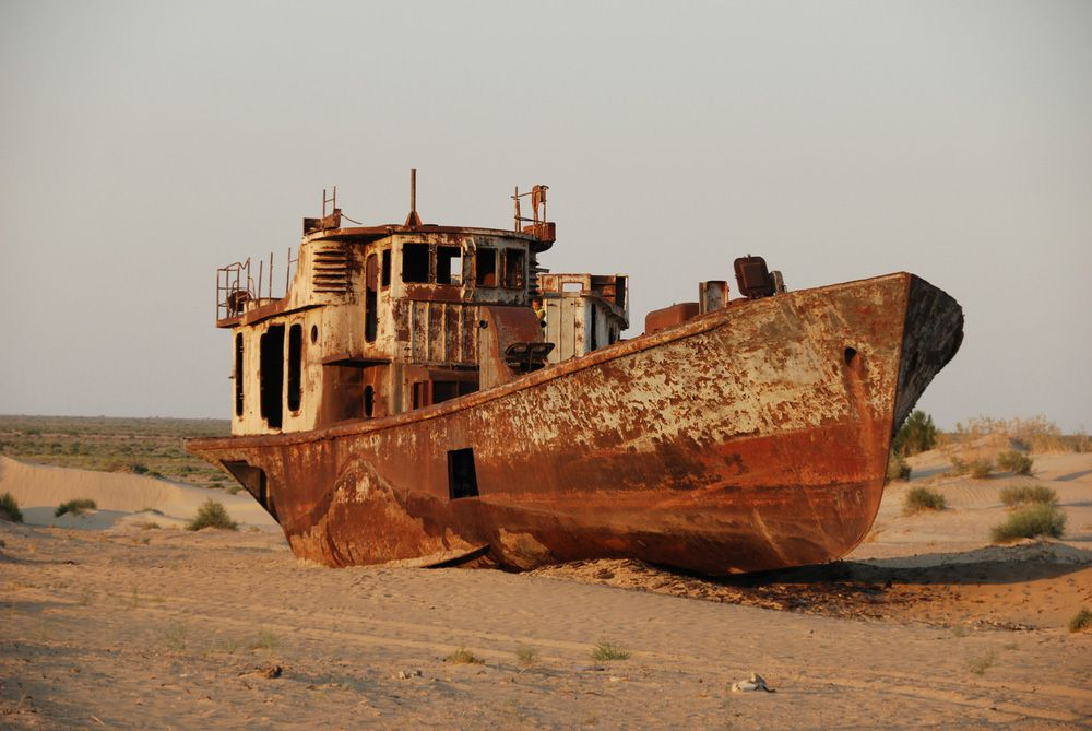 A rusted, abandoned ship in a sandy desert that was once a lake