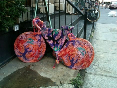 bike with crochet cover leans against stair railing on city street