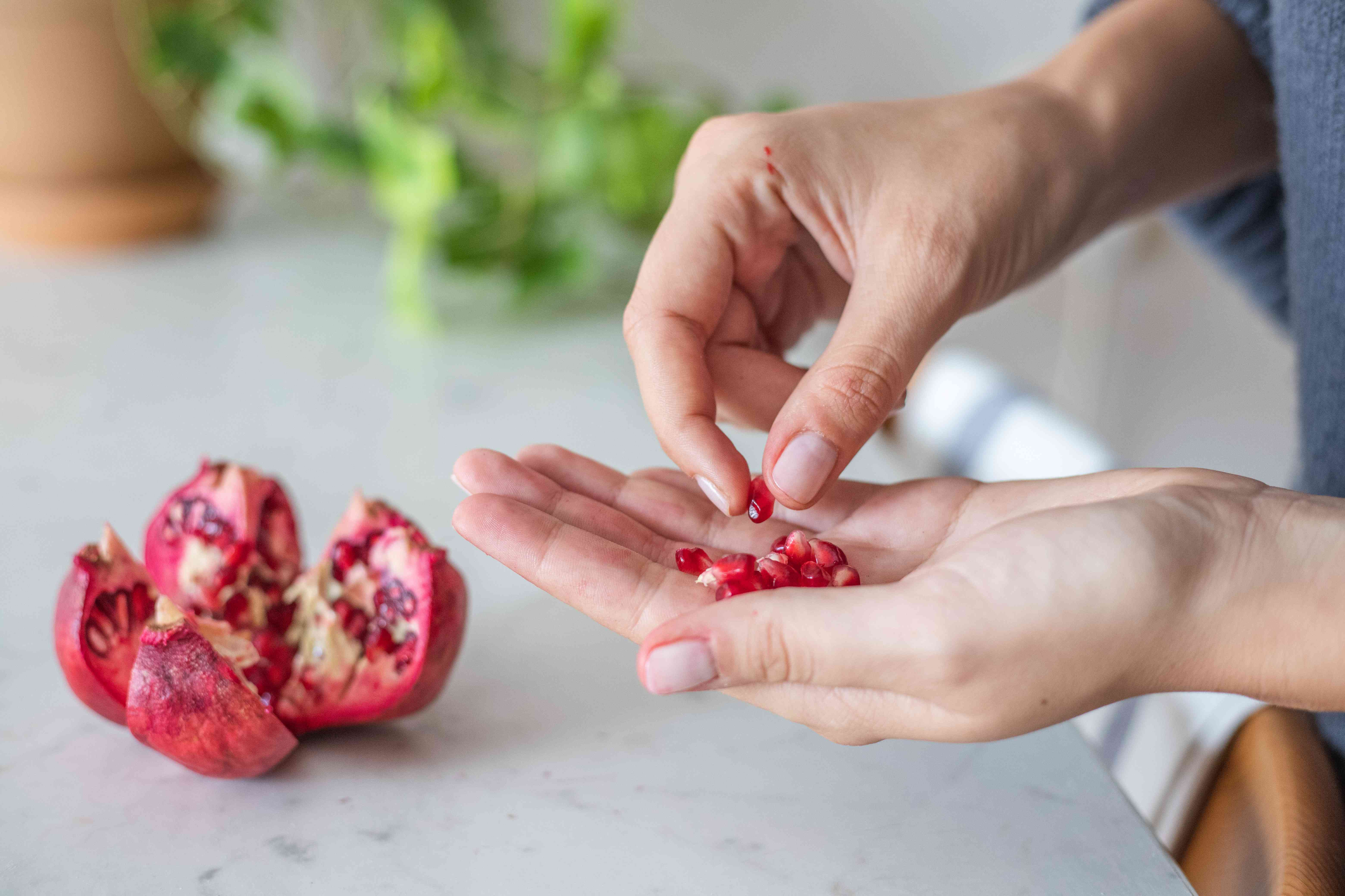 person picks out seeds with cut pomegranate on white marble kitchen countertop