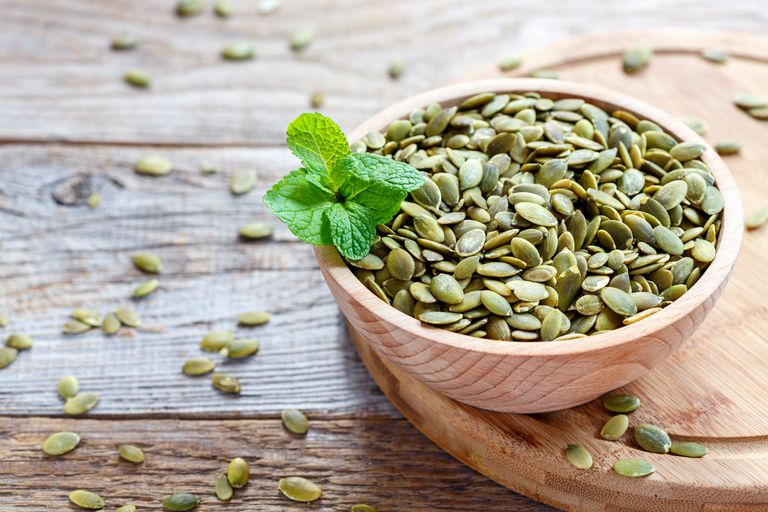 bowl of pumpkin seeds on a wooden table