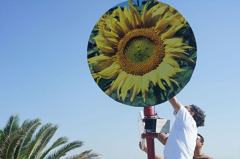 man adjusts bladeless saphon turbine against sky