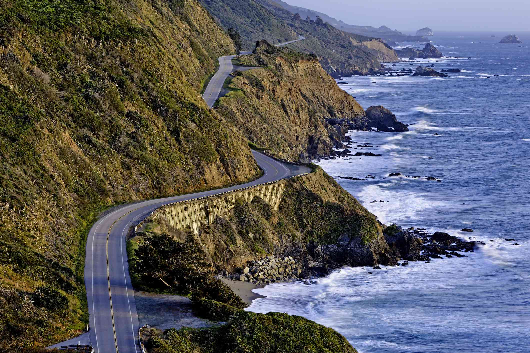 Pacific Coast Highway running along rocky coast at sunset