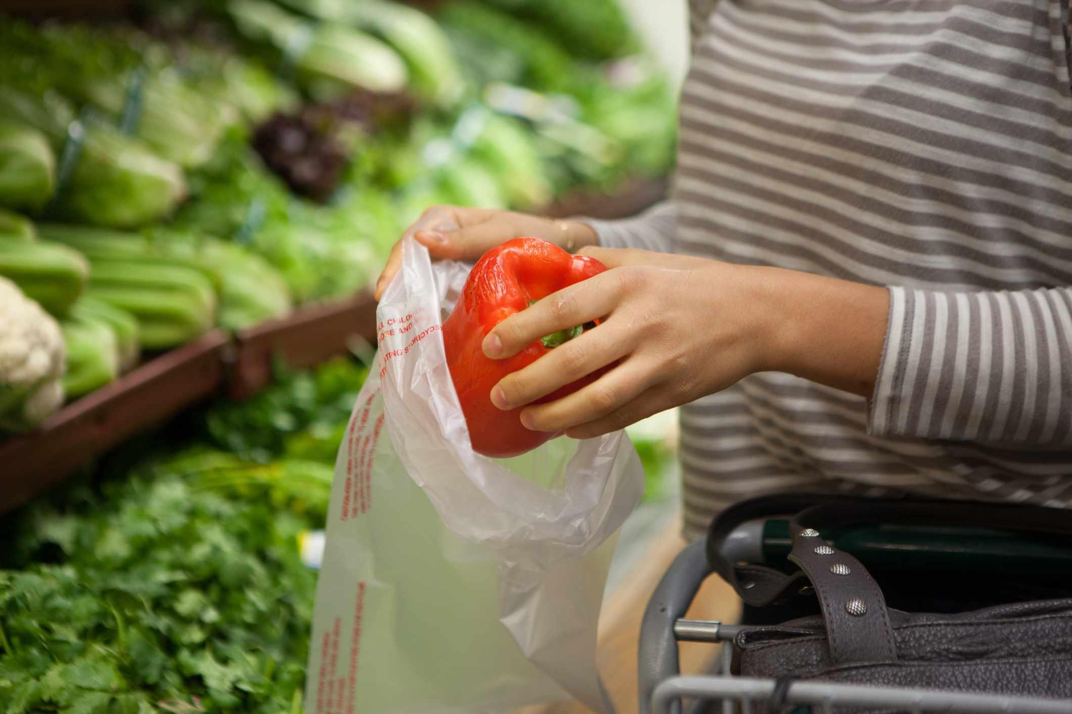 A woman puts a red pepper in a plastic bag.