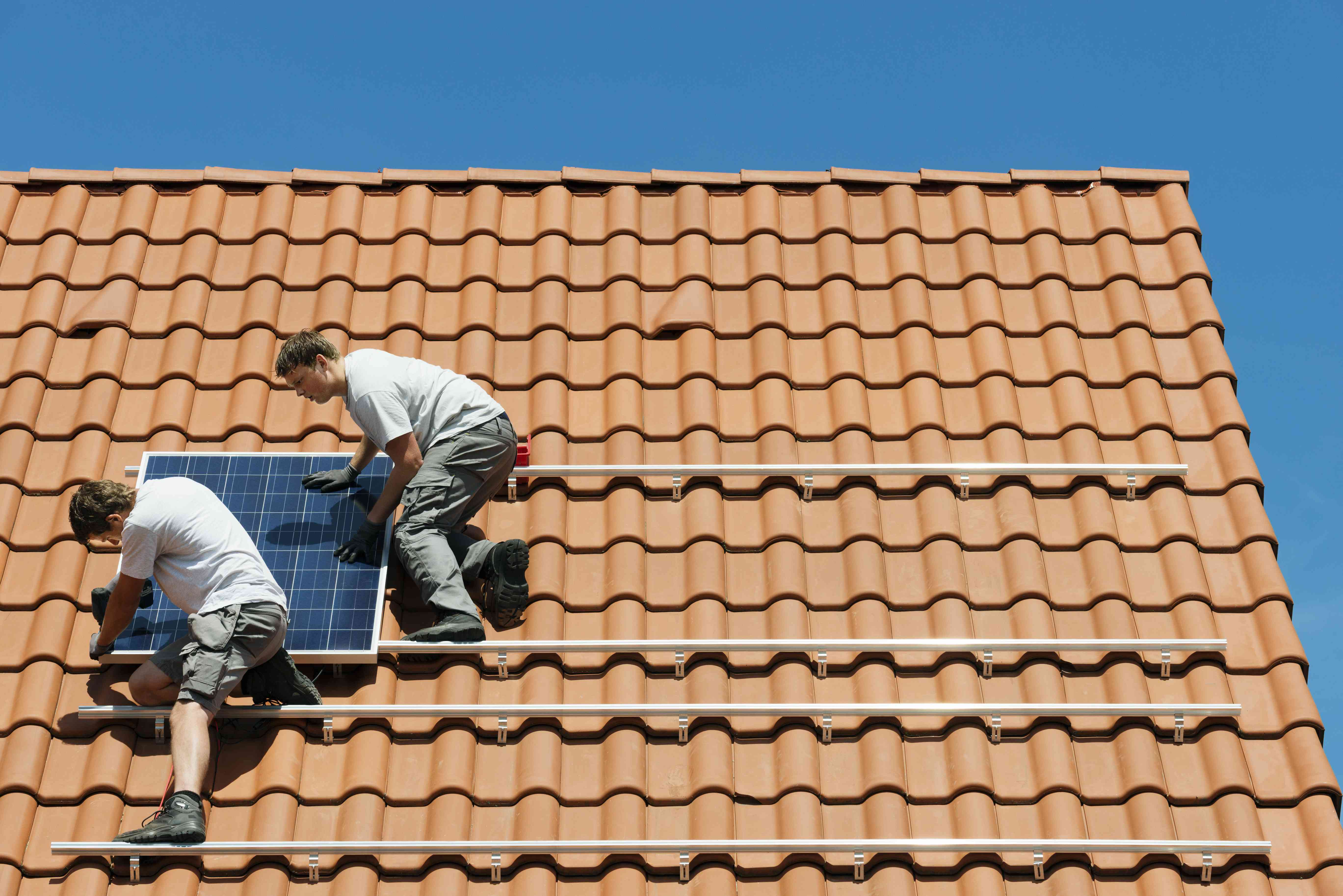 Workers installing solar panel on roof framework of new home, Netherlands