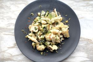 Cooked cauliflower on a plate including florets, stems, and leaves