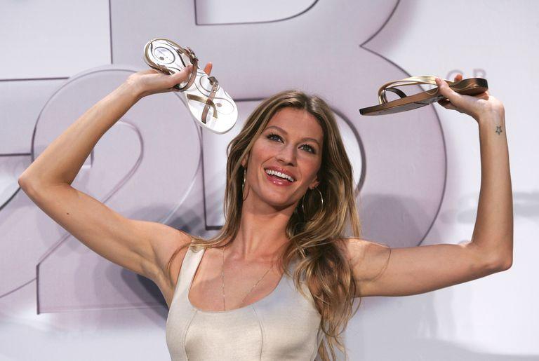 Model Gisele Bundchen holding up flop flop sandals.