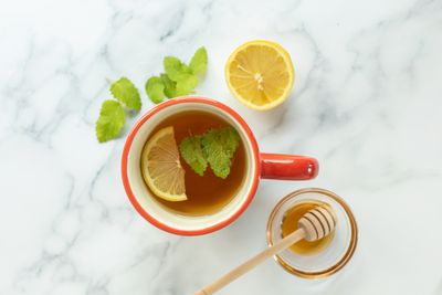 cup of tea with lemon and honey and fresh lemon balm leaves