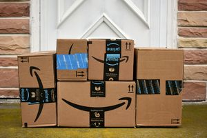 Stack of five Amazon Prime boxes in front of a white door