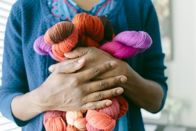woman holding skeins of wool