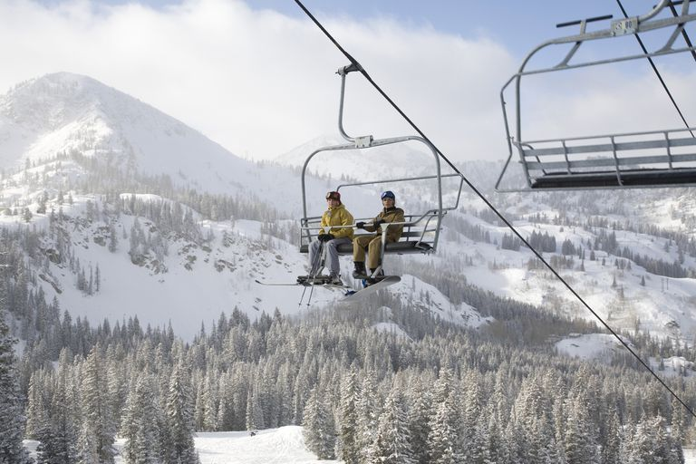 Skiers on a lift going up a mountain.