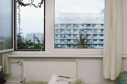 Open apartment window, plants visible on a balcony