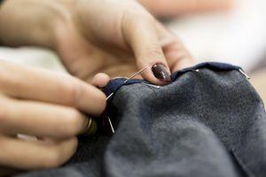 woman's hands sewing denim