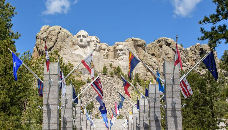The 56 state, district, commonwealth, and territory flags on concrete columns surrounded by tall green trees in front of Mount Rushmore below a blue sky with white doulds