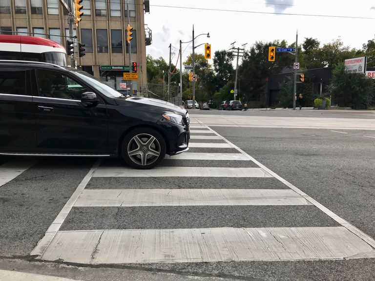 Car at stop light sitting on top of pedestrian crosswalk