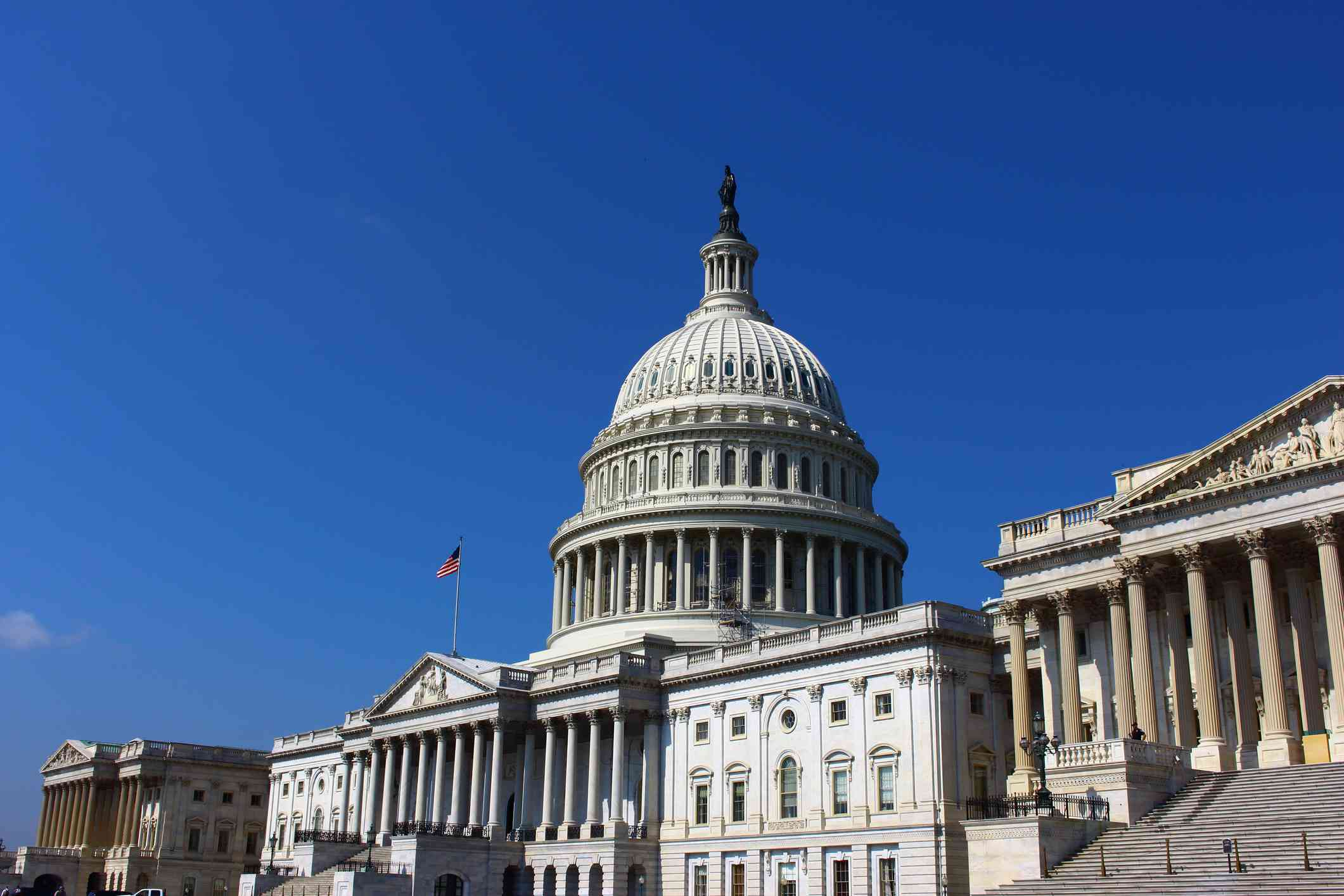 Low angle view of Capitol building in Washington D.C. against a clear blue sky