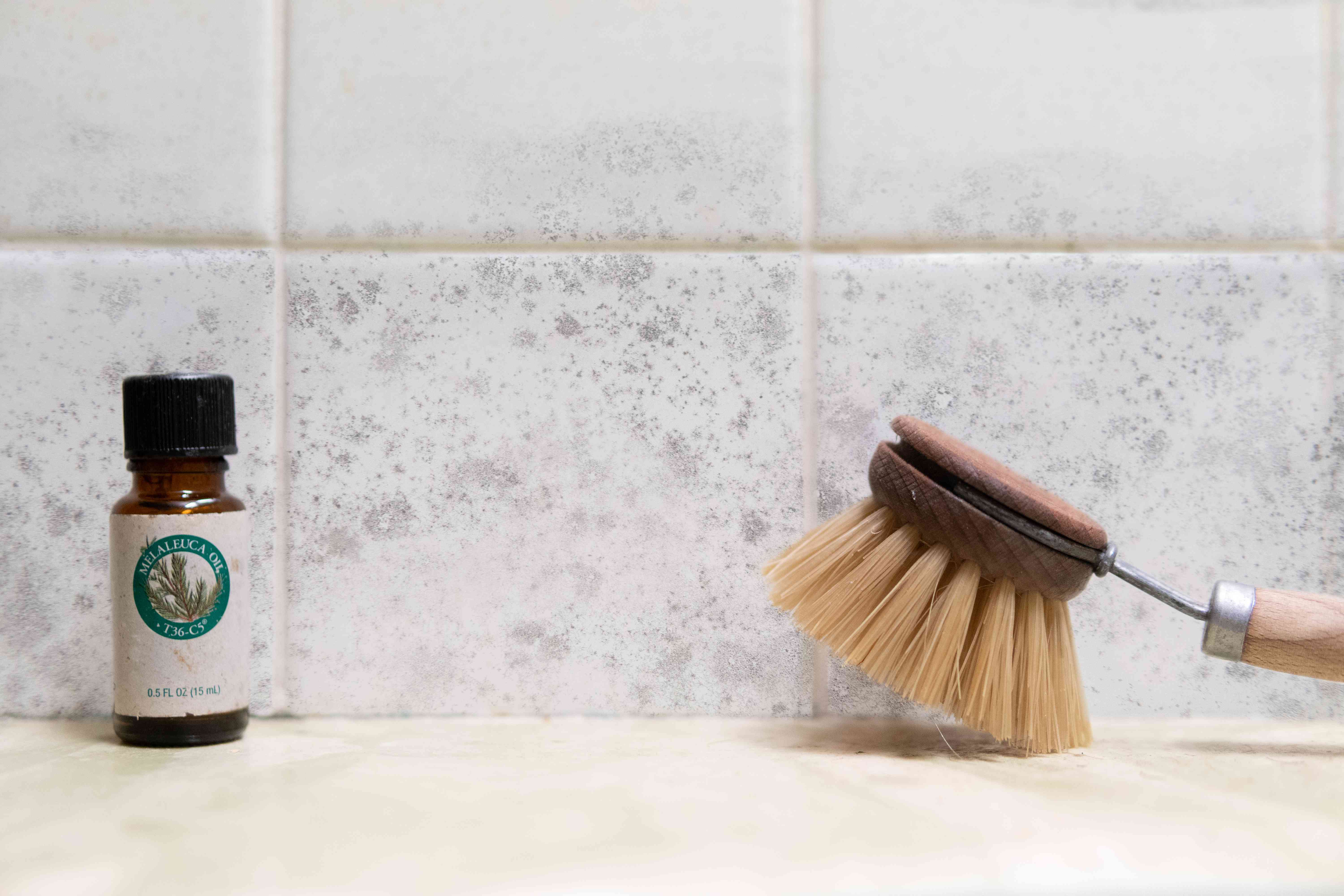 tea tree oil with wooden scrubber in shower