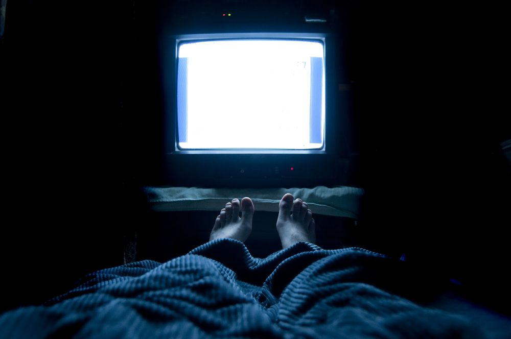person watching tv at night in bed