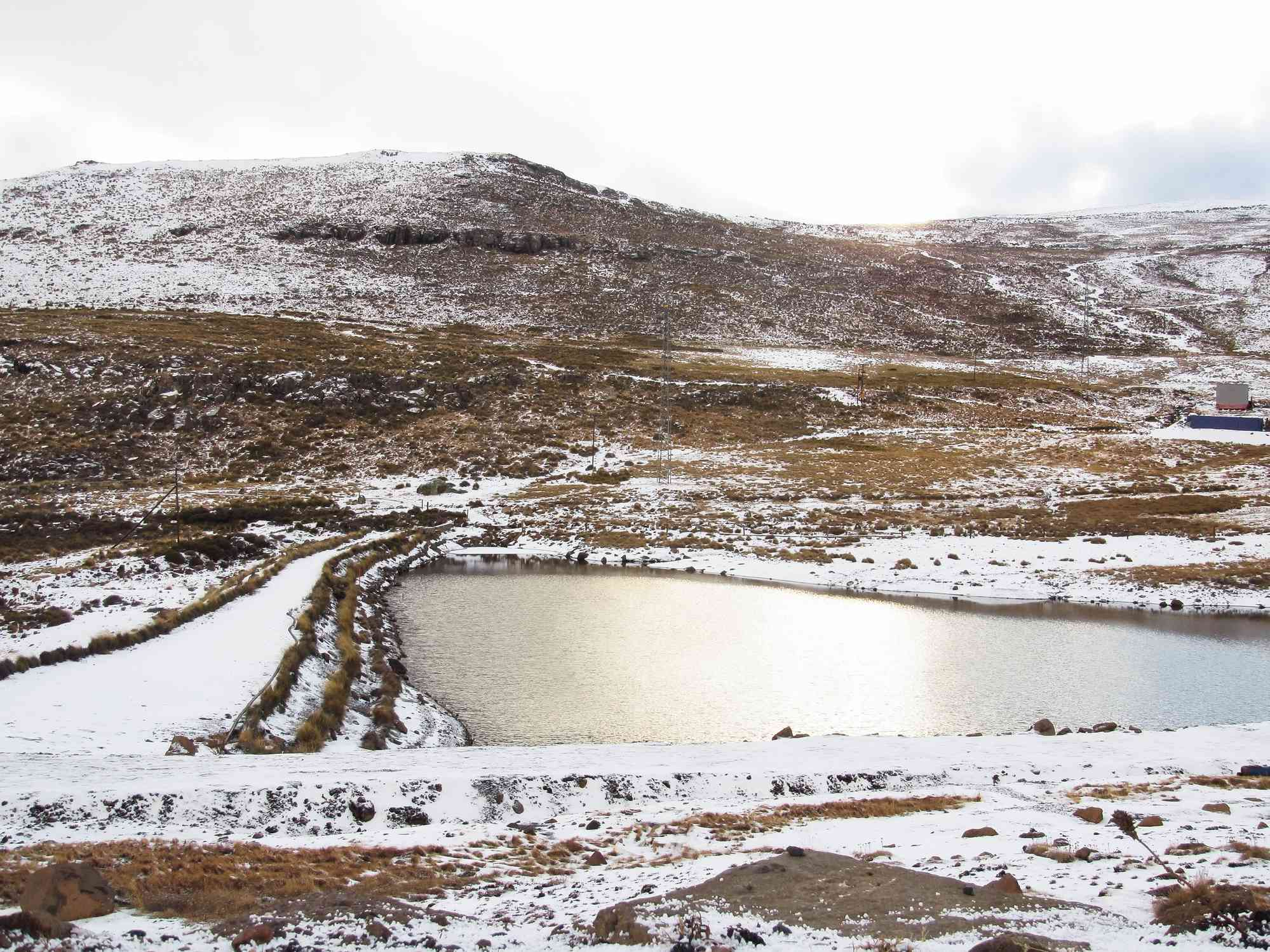 View of Maluti mountains lightly covered in snow, with portions of the brown grown below showing through, with a lake in the center during winter season in Lesotho.