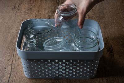 hand recycles glass jars in tub