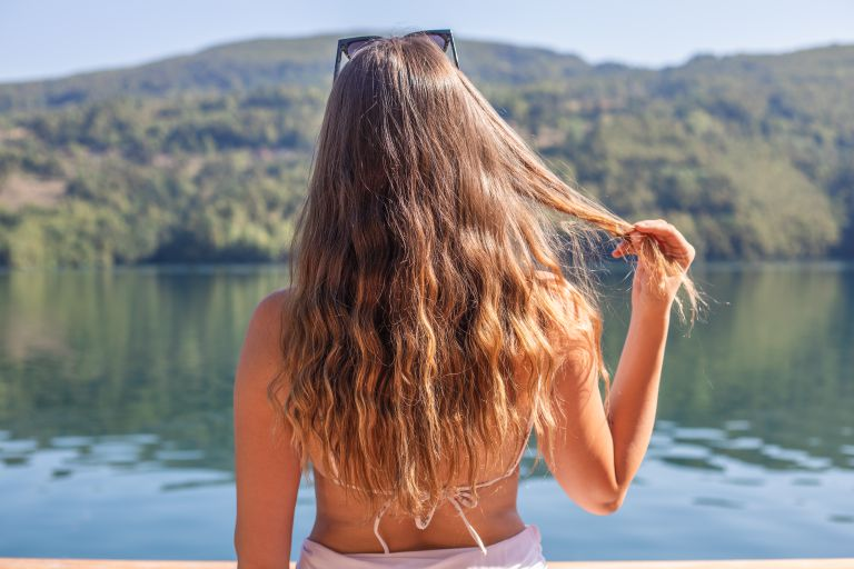 woman in swimsuit plays with long hair while looking out at large lake