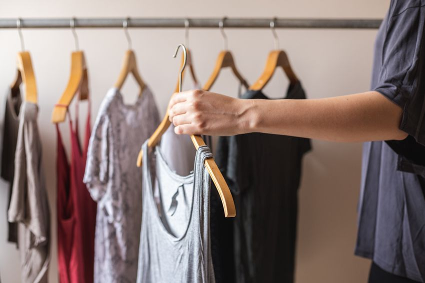 person picks up tank top amongst used clothing on wooden hangers
