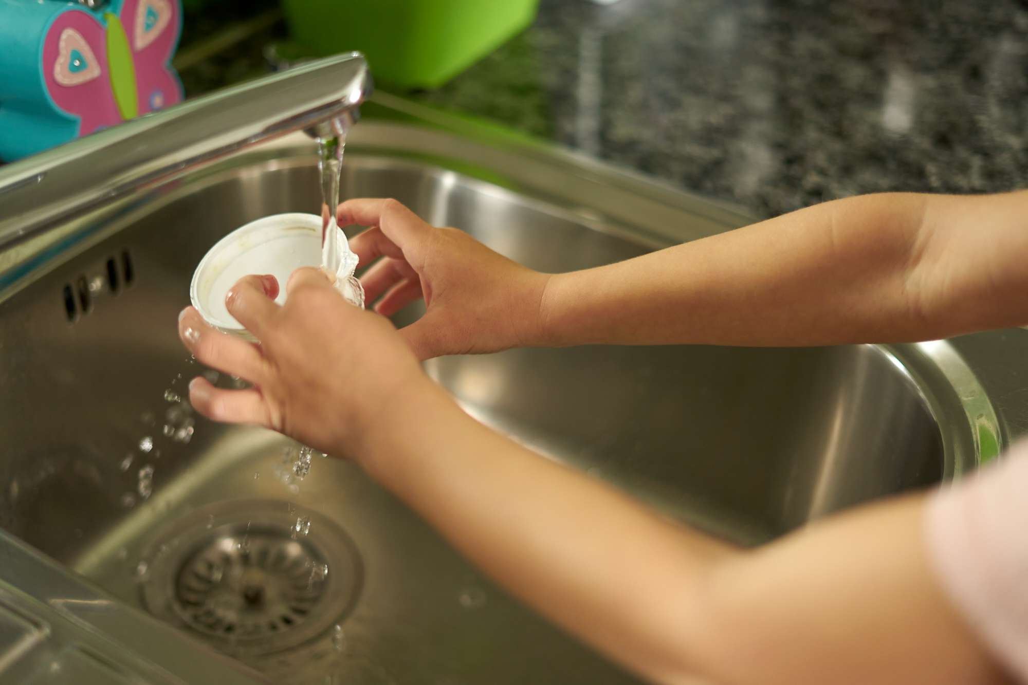 kid's hands rinse out plastic cup in kitchen sink before recycling