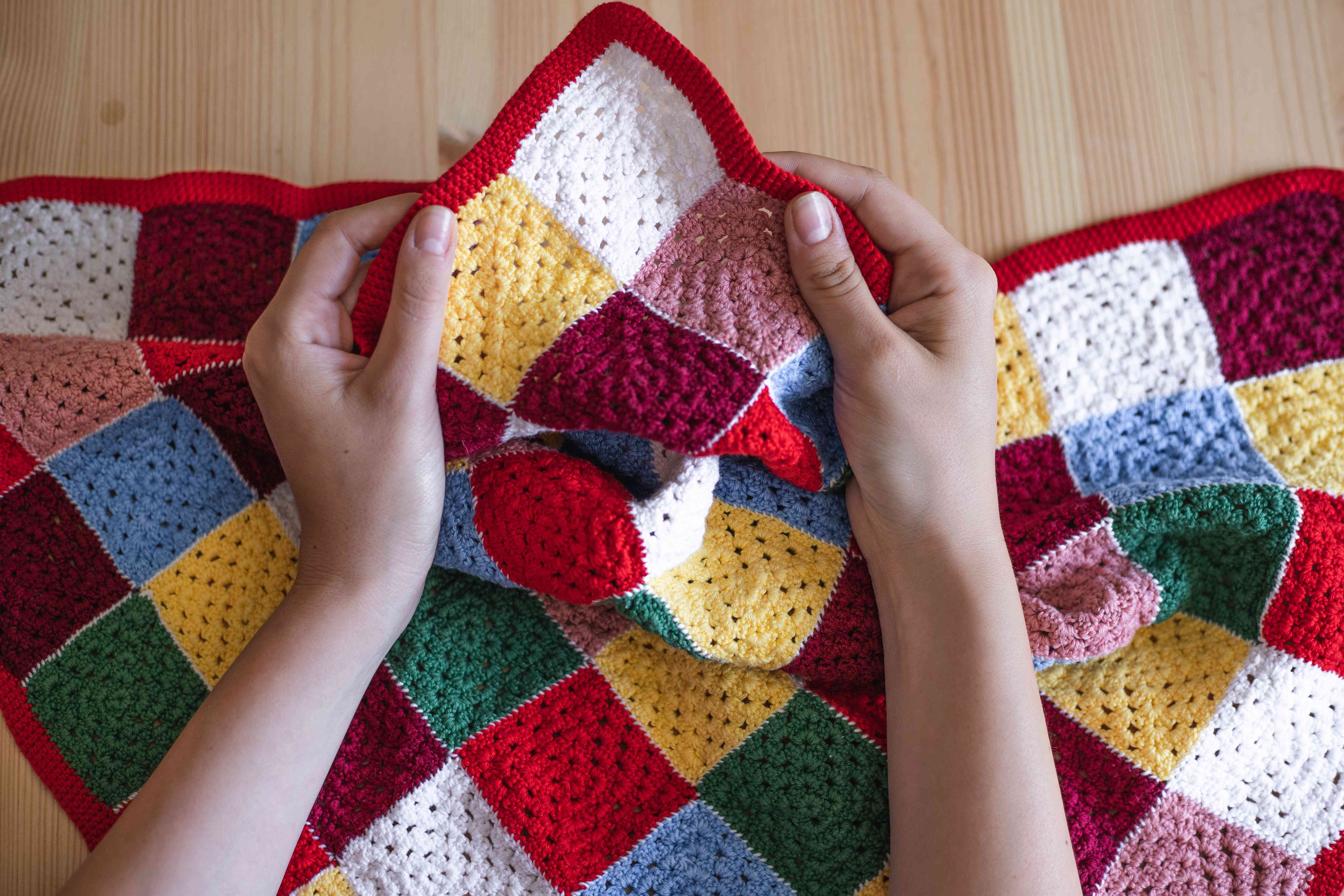 hands hold up a crocheted handmade blanket with multicolor squares