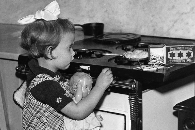 Little girl cooking on gas stove