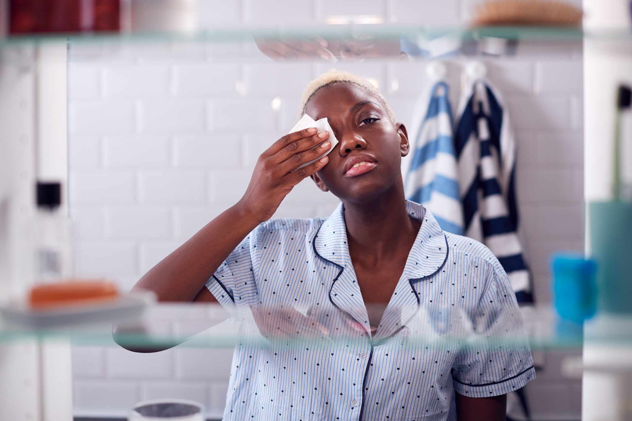 A young black woman cleans her face off looking in the bathroom cabinet.