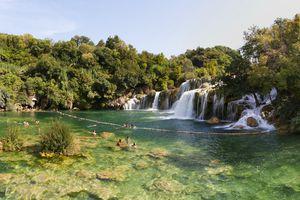Swimmers bathe in the clear waters of Skradinski buk in Croatia
