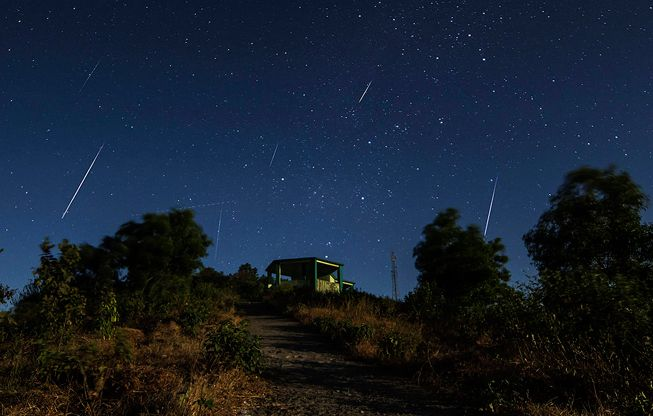 Geminid meteors streak over a green structure in the Northern Hemisphere